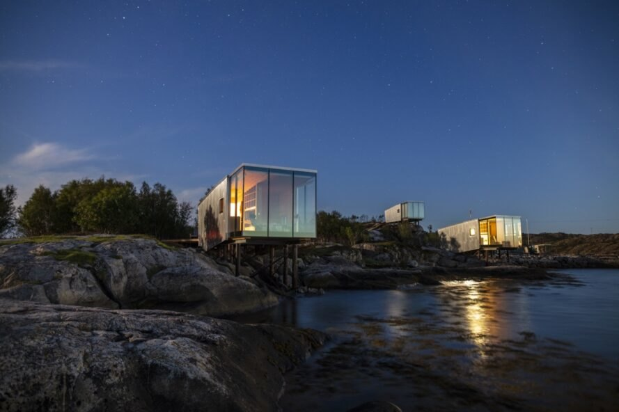 glass and aluminum cabin lit from within at night