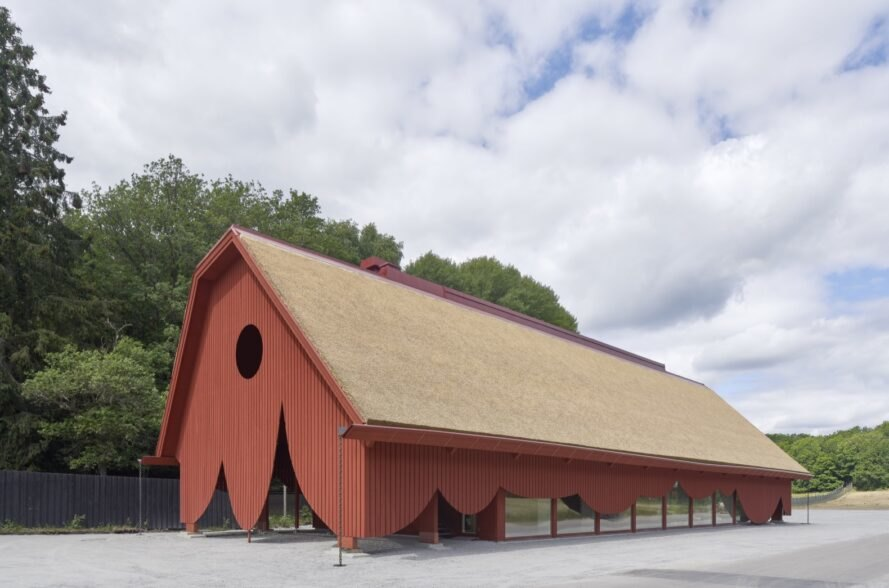 red barn inspired building surrounded by large green trees