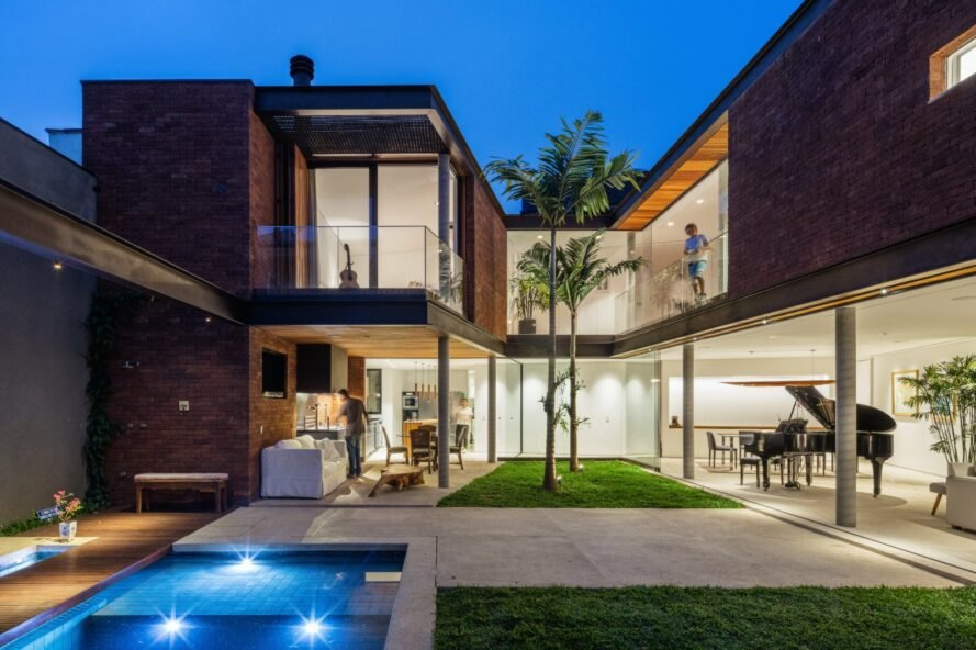 brick and glass home with small pool and courtyard