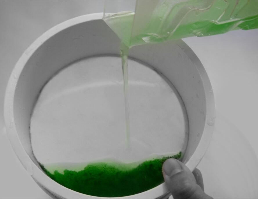 person pouring green liquid into a dish