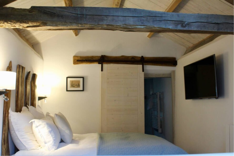 bedroom with wooden beams exposed in the ceiling