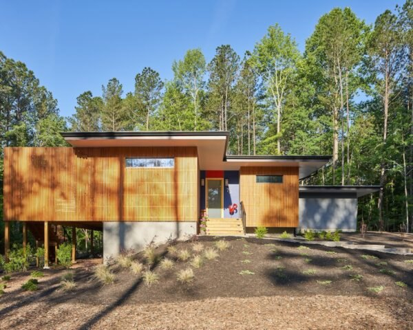 modern single story wood home surrounded by trees