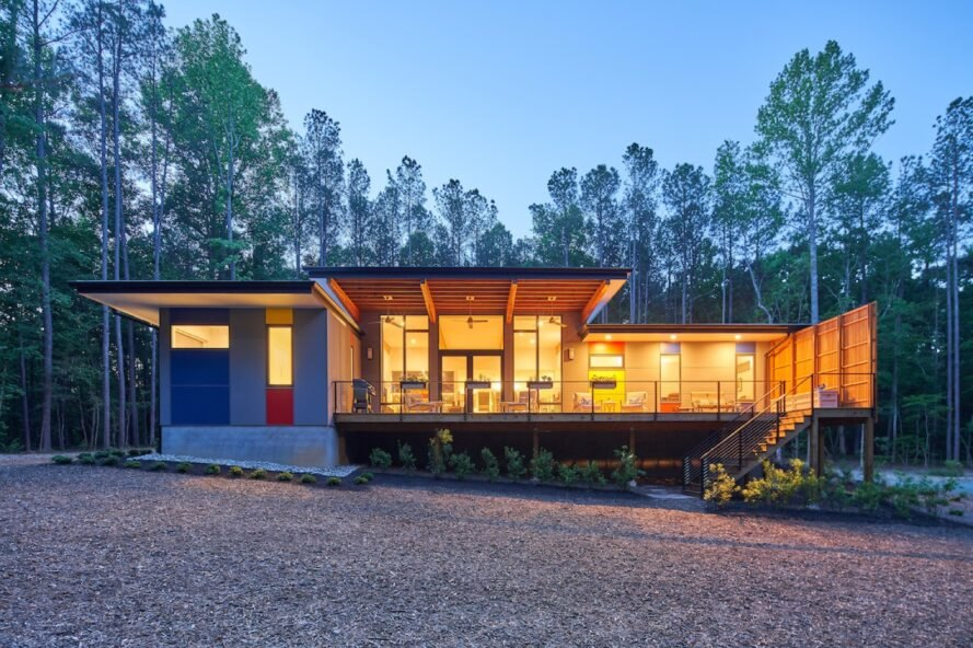 modern single story wood home surrounded by trees with large windows