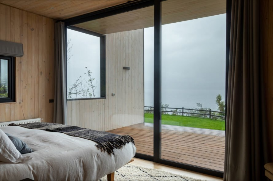 bed facing glass wall and wood deck