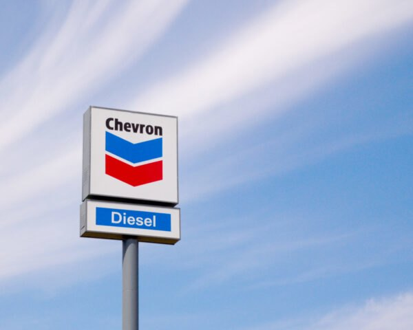 Chevron gas station sign against blue skies
