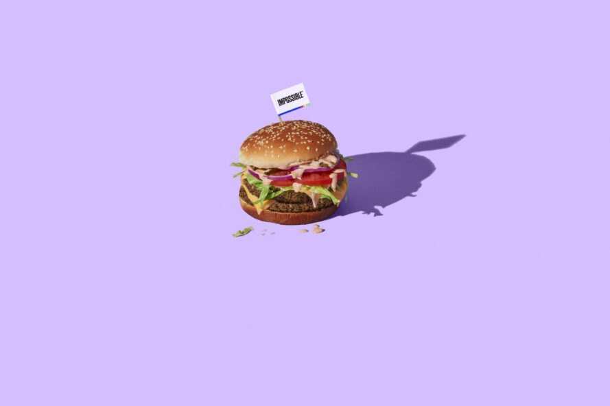 purple background with vegan hamburger with tiny white impossible flag