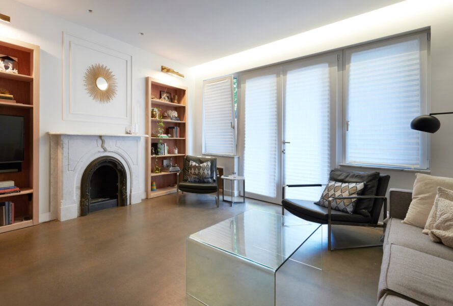 white living room with wood bookshelves and old white fireplace