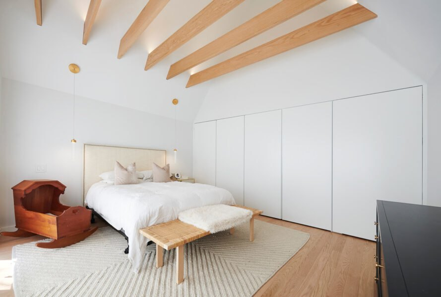 large white bedroom with light wood ceiling beams