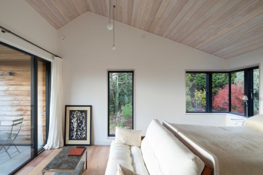 light filled room with white walls, wood ceiling and floors and multiple windows