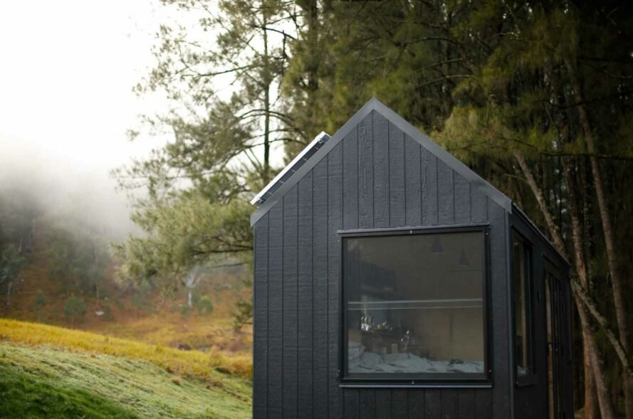 tiny black cabin with pitched roof and large window