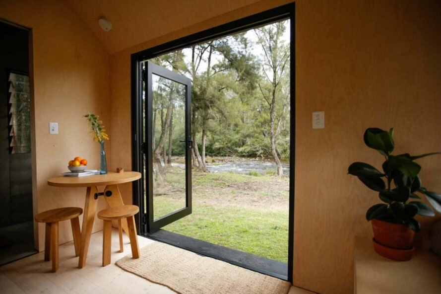 interior of tiny cabin with large glass door open to the outdoors
