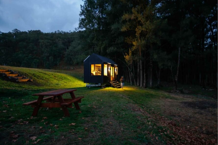 tiny black cabin with pitched roof with solar panels