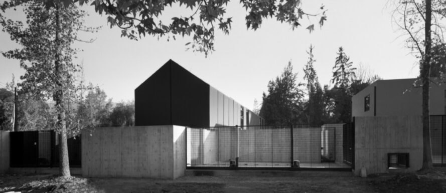 black and white photo of elongated black home with gabled roof