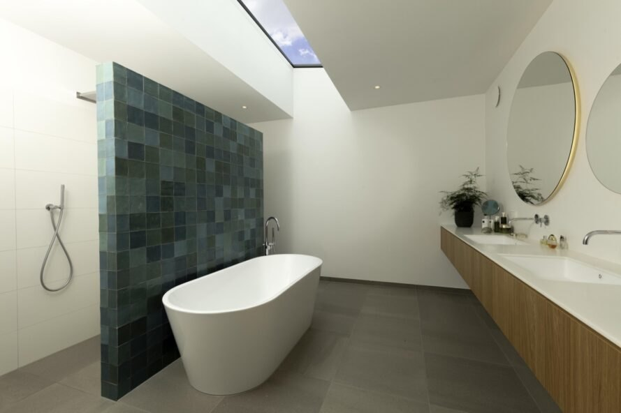 bathroom with freestanding tub and wall of blue tiles