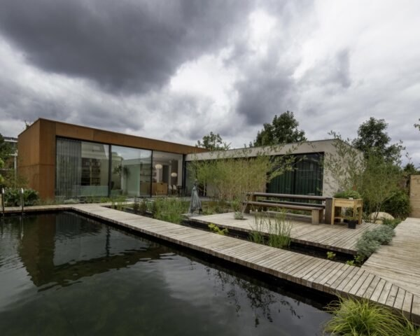 home with weathered steel exterior and wood walkway over a natural pool