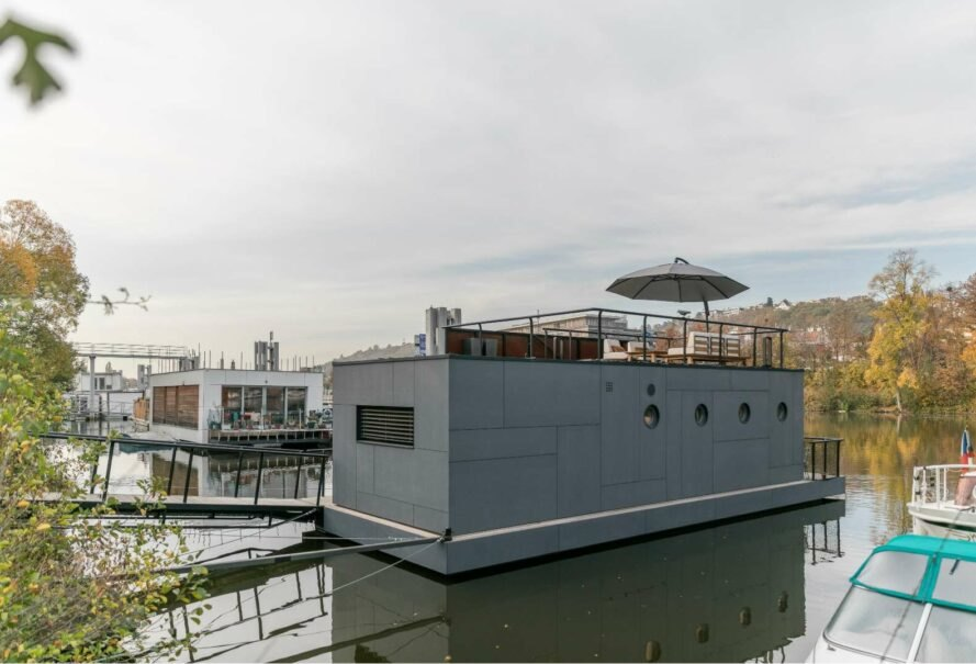 houseboat with wood and cement facade and roof deck