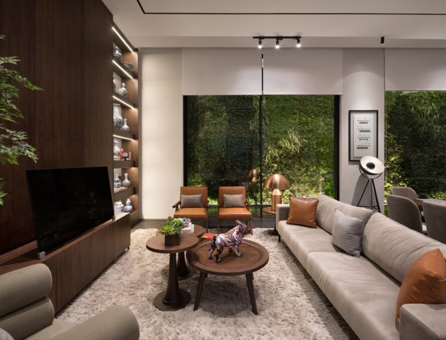 gray sofa facing dark wood wall with TV and bookcase with windows revealing a green wall