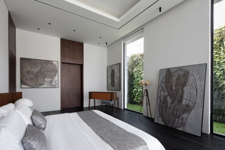 white bedroom with large pieces of artwork