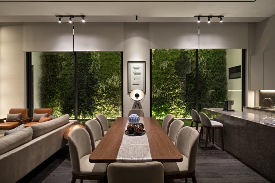 wood dining table in front of tall windows with views of a green wall