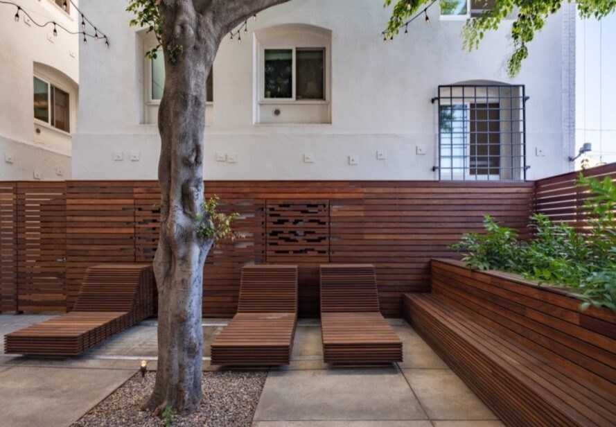 wood lounge chairs and tree in courtyard