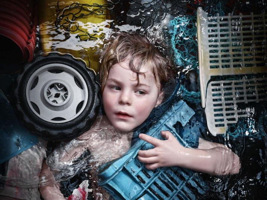 portrait of child drowning in plastic waste
