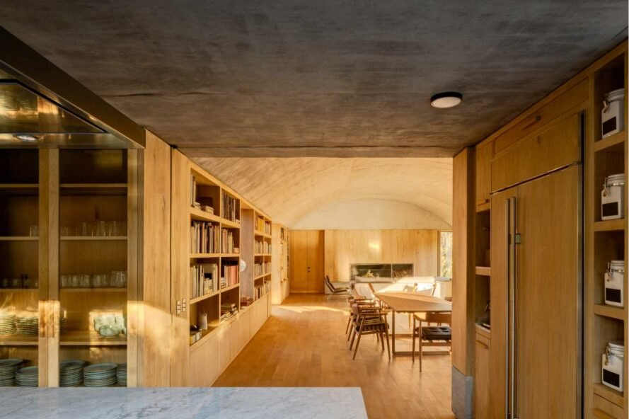 room with wood floors and walls and large wall of books