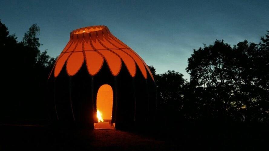 round, pod-like shelter with fire pit in center