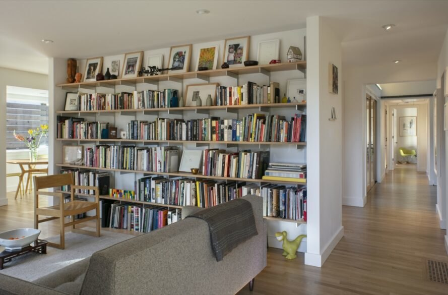 interior of home with bookcase on white wall and wooden floors with gray couch