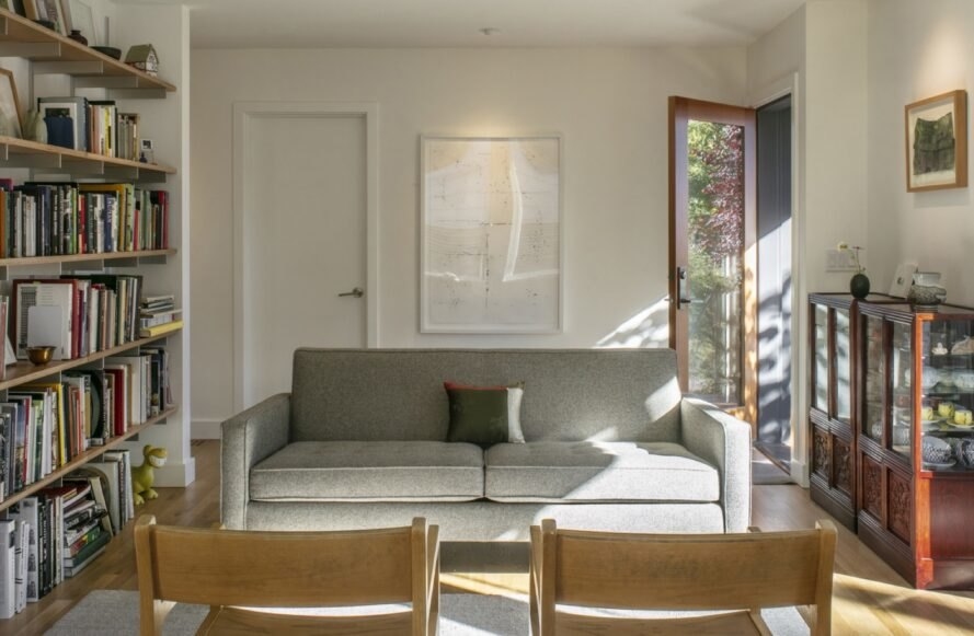 gray couch beside large window and glass door with wooden trim and white walls