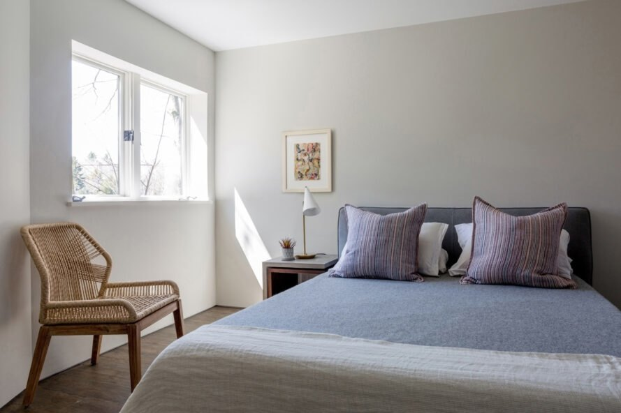 bedroom with gray bed and wicker seat