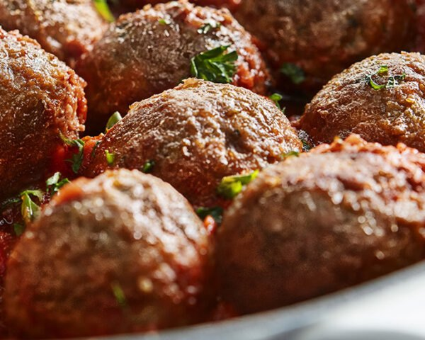 Beyond Meat plant-based meatballs simmering in a pan of marinara sauce