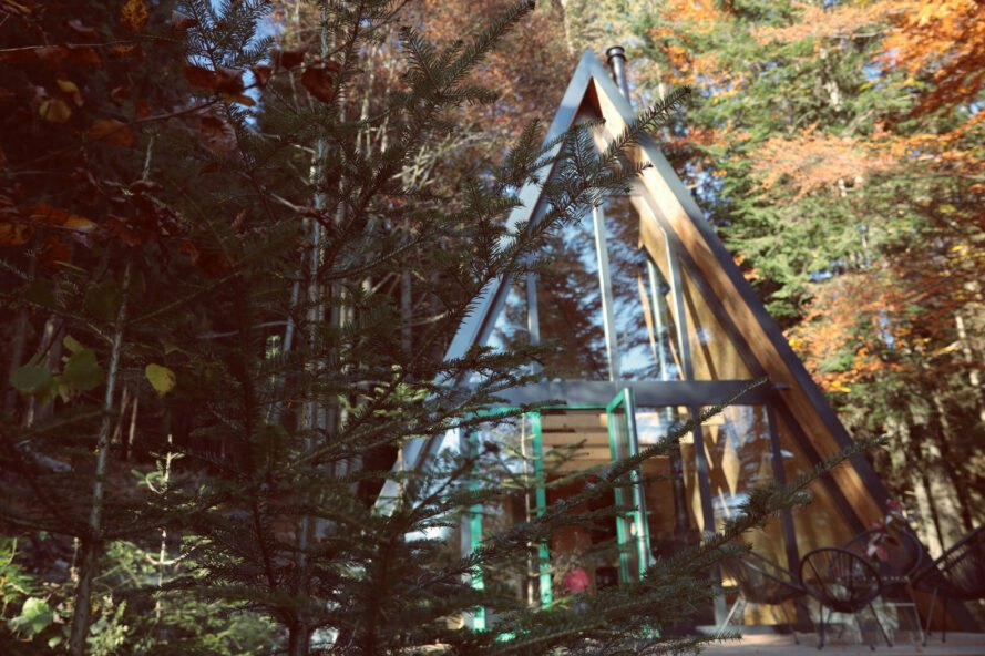 dark A-frame cabin with wall of glass