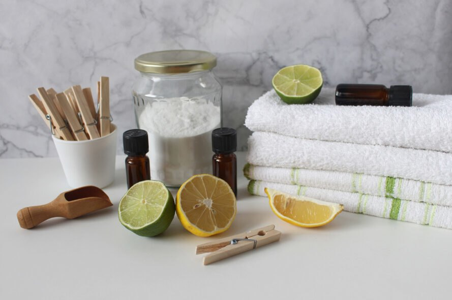 towels, homemade detergent and lemon and lime wedges on white table
