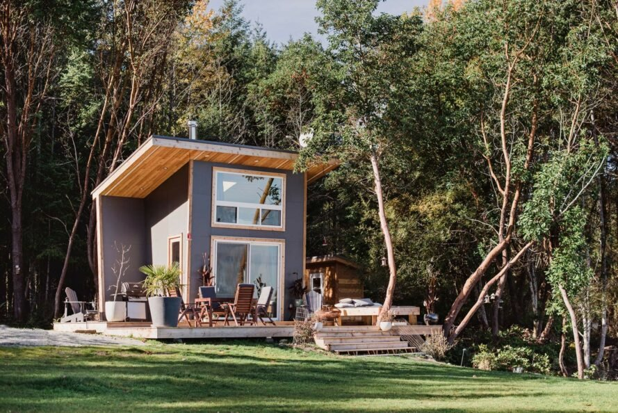 tiny gray home in front of forested area