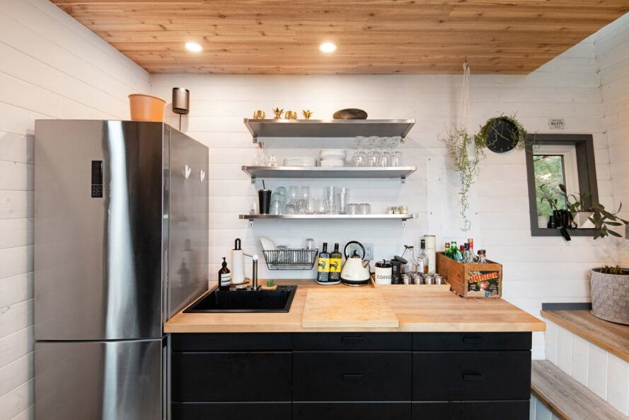kitchen with stainless steel fridge and dark cabinets with wood countertops