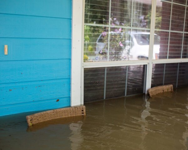 front porch of blue home flooded with stormwater