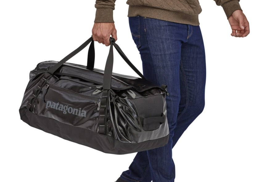 person carrying black duffel bag