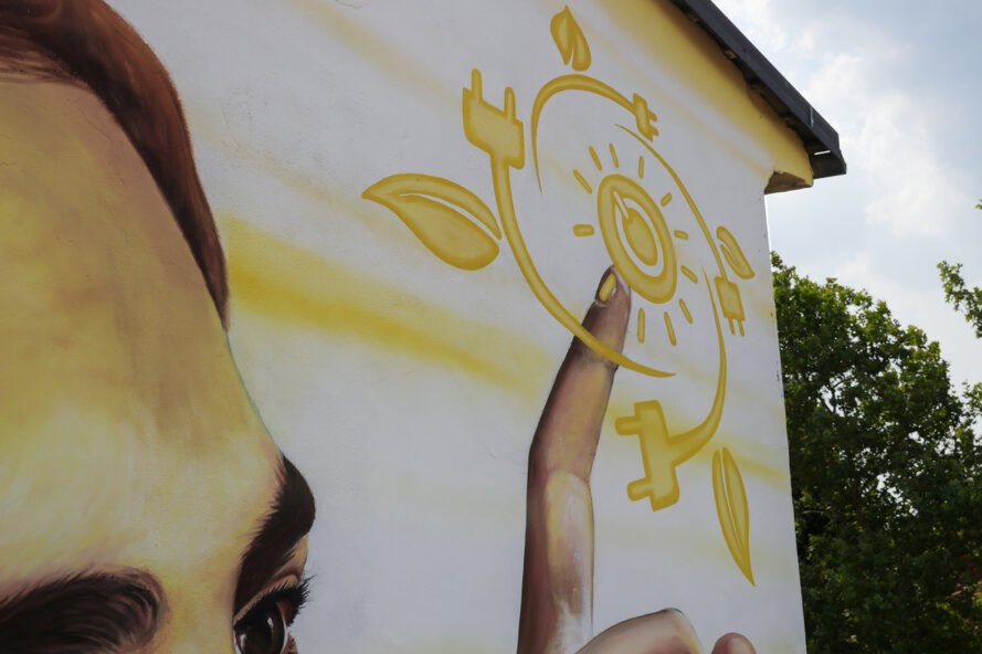 painting of hand touching symbols like a sun and a leaf on a wall