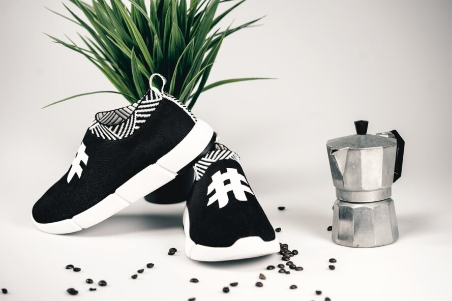 black and white sneakers beside an espresso maker