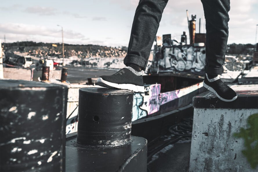 person climbing in black and white sneakers