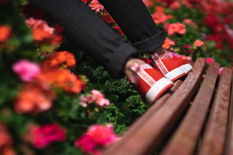 person walking on top of wood bench near floral bush in red sneakers