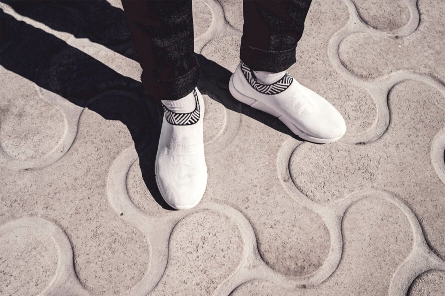 white sneakers against patterned sidewalk