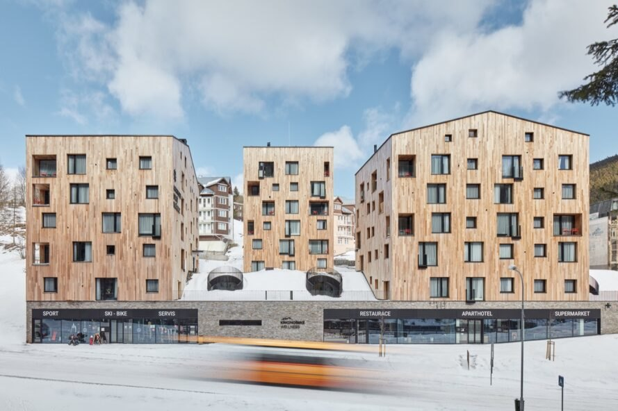light wood buildings with misaligned square windows on snowy landscape