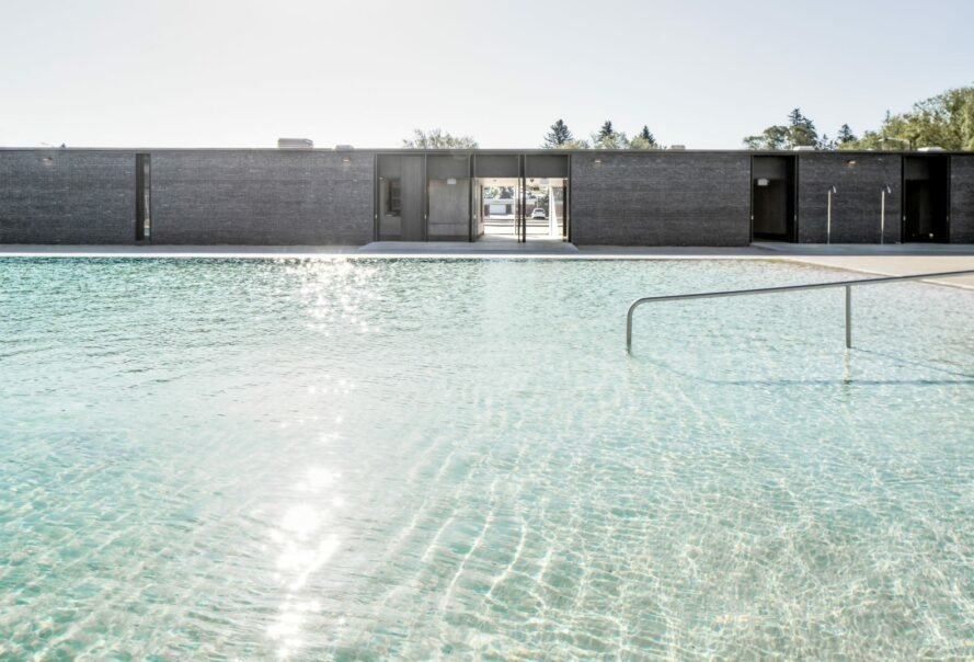 large swimming pool with slate grey building in the background
