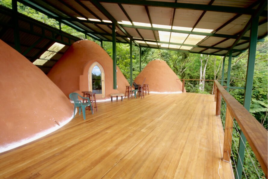 rammed earth domes connected by a wood deck