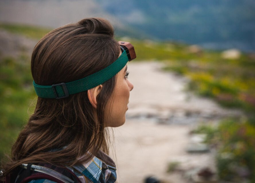 woman wearing headlamp on a hiking trail