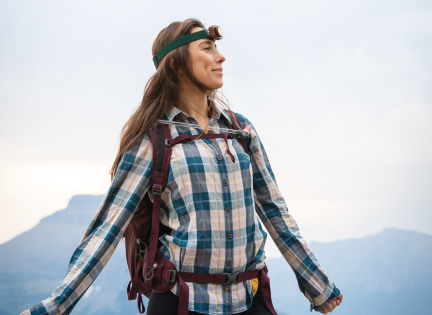 woman wearing headlamp with mountains in background