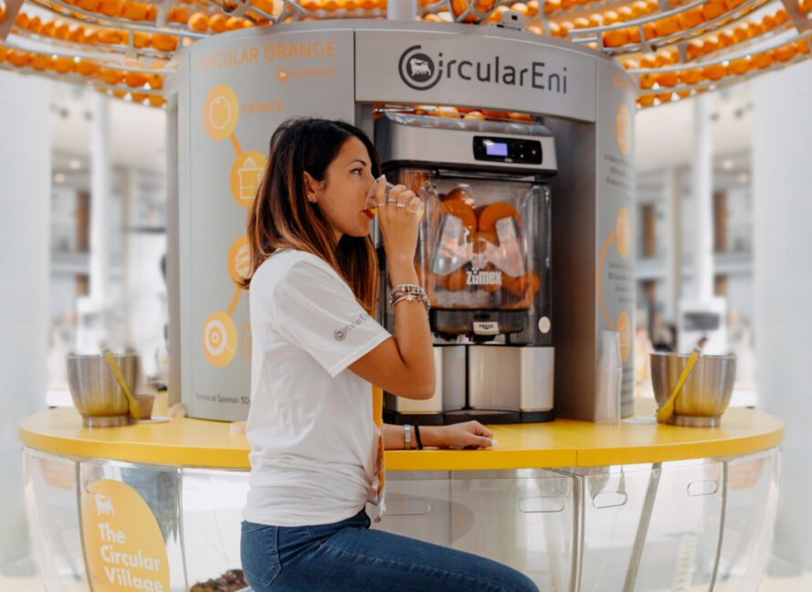 woman drinking orange juice at machine
