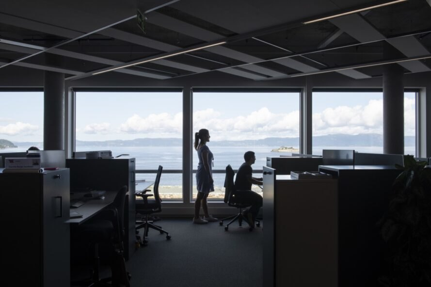 people working at desks in room with water views