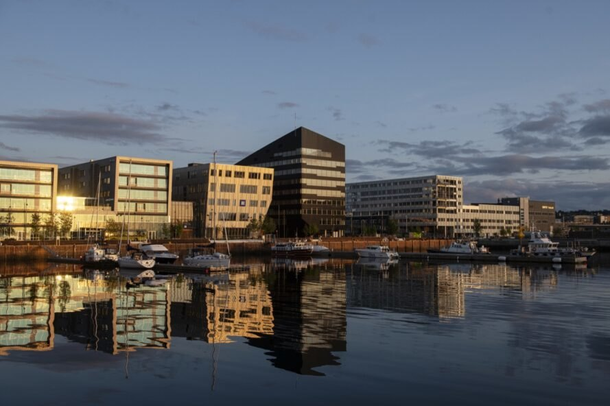 dark metal-clad geometric building and traditional office buildings near water at dusk